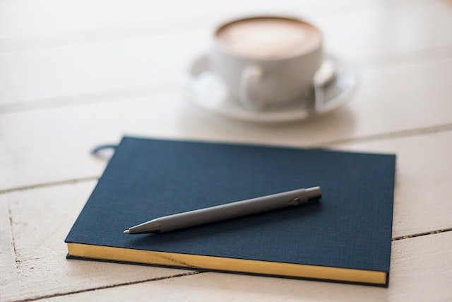 Notebook with pen on a desk next to a cup of coffee